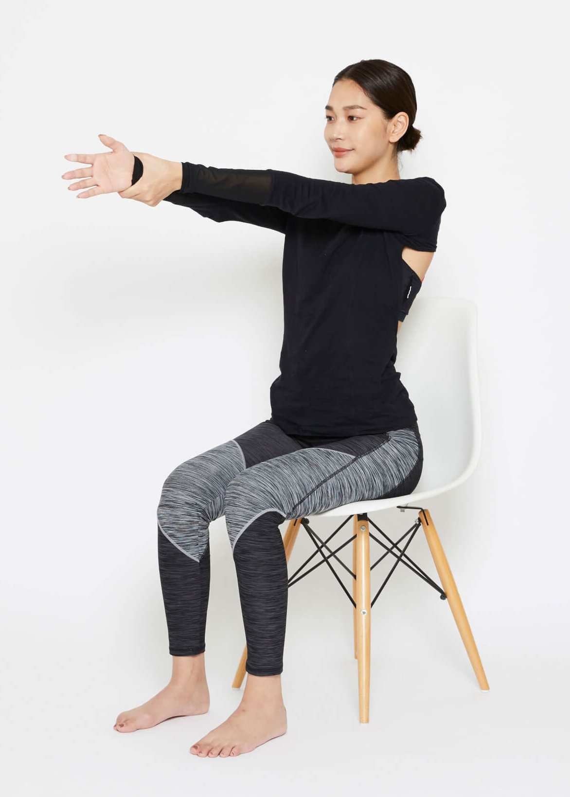 「1.イスに座り片方の手を伸ばします。もう片方の手で、伸ばした手の手首を掴みます。」を説明する画像