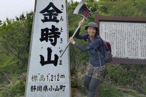 金時山の頂上にある「天下の秀峰 金時山」と書かれた看板をバックに「まさかり」を担いだ高島麻利央さんの写真