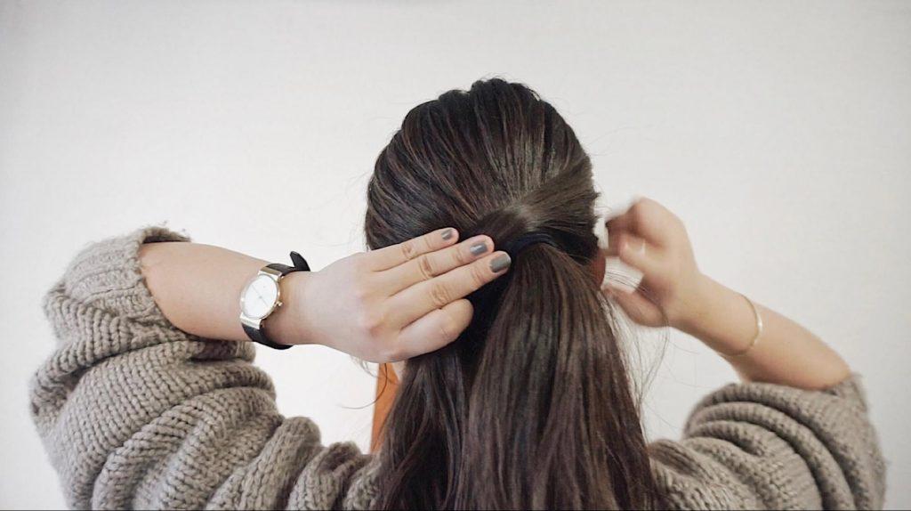 手順3「サイドにわけておいた毛束を、上から逆サイドに向かって、ゴムが隠れるように巻きつけていきます。」を説明する写真
