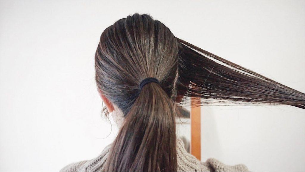 手順1「まず、サイドの毛をひとつかみくらいの量に分けとり、残りはポニーテールにします。」を説明する写真