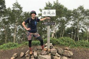 赤城山のパワースポットの前に立つ高島麻利央さんの写真
