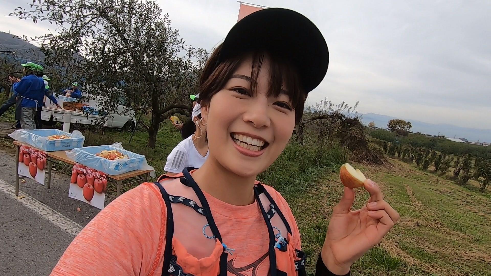 中村優さんがマラソン大会中にリンゴを食べている写真